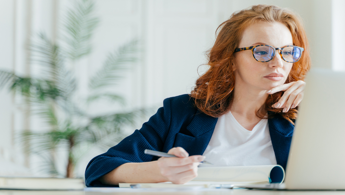 Woman Coach Sitting at desk looking at computer in office