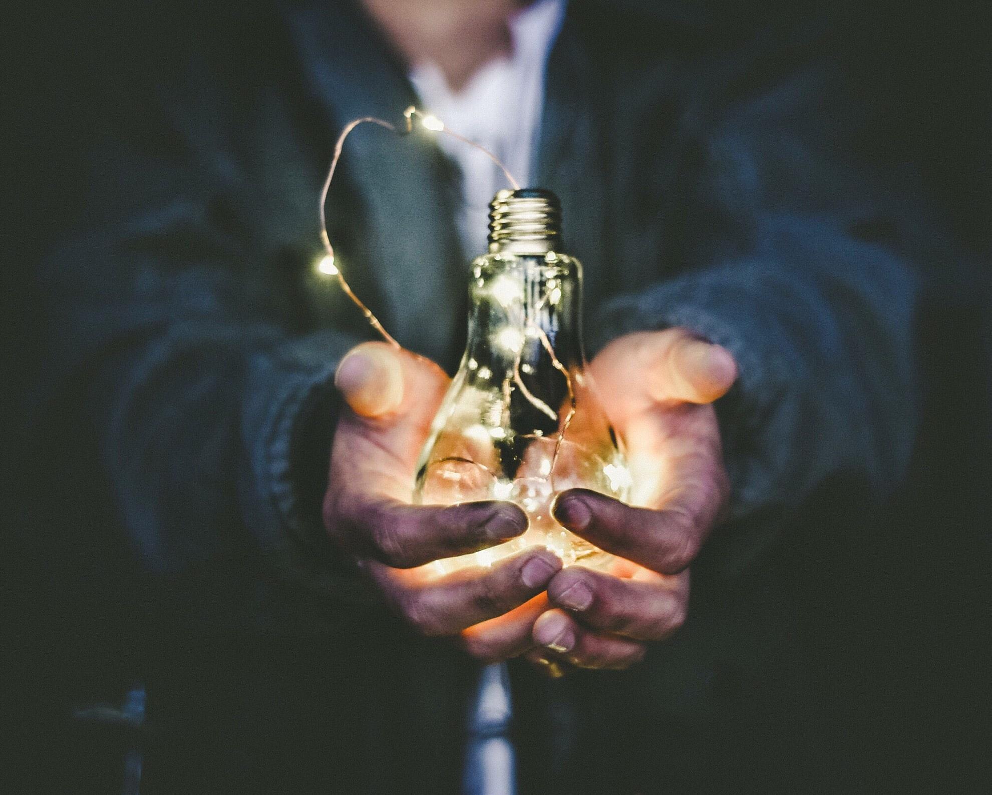Hands holding a light bulb.